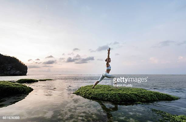 young woman practicing yoga on seashore