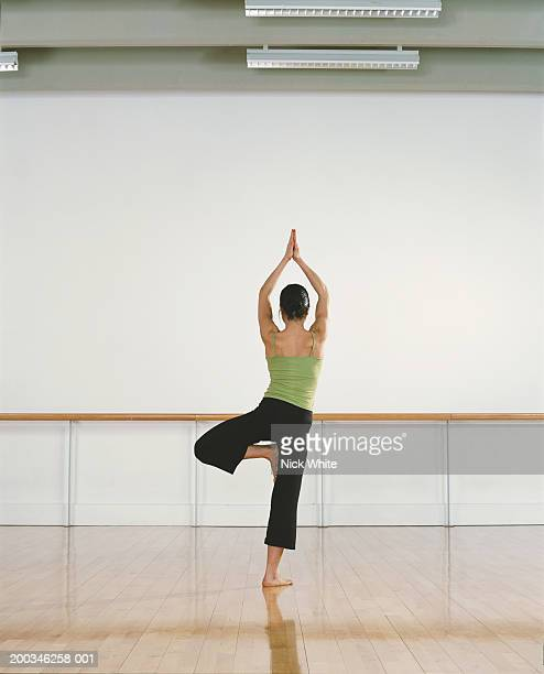 young woman practicing yoga position in dance studio, rear view - tree position stock photos and pictures