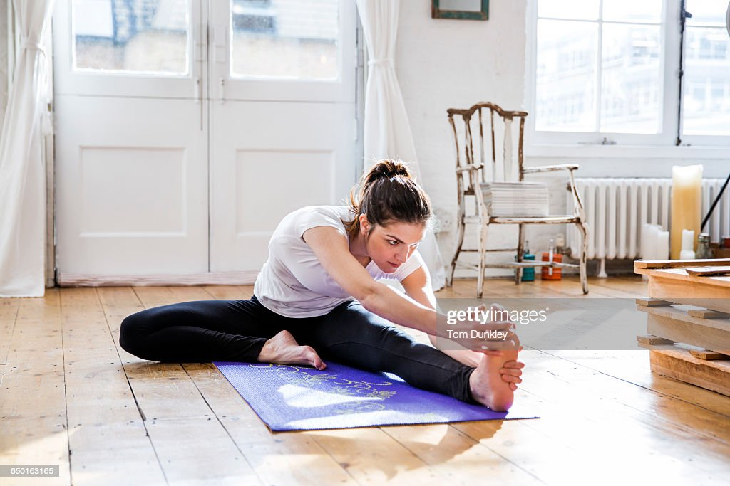Young woman practicing yoga, touching toes in apartment : Foto de stock