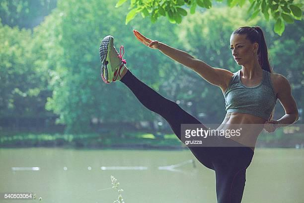 Young woman practising karate balancing on one leg