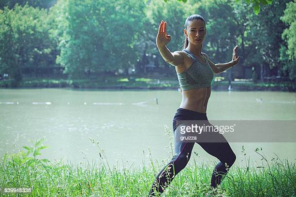 Young woman practising karate on the waterfront