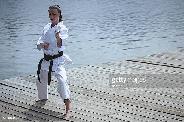 Young woman practising karate outdoors