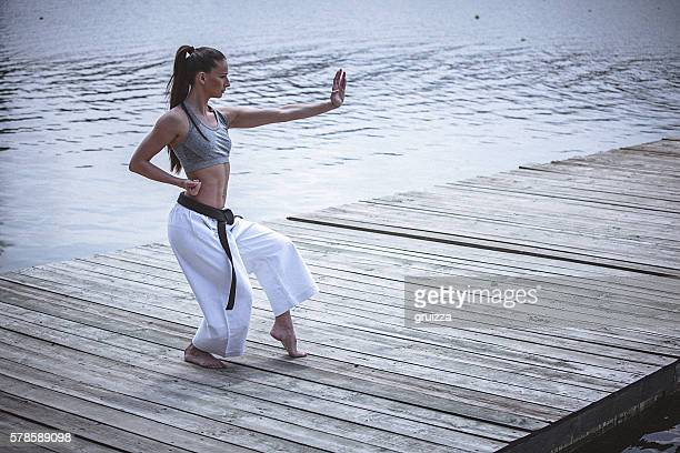 young woman practising karate outdoors - adults only stock pictures, royalty-free photos & images
