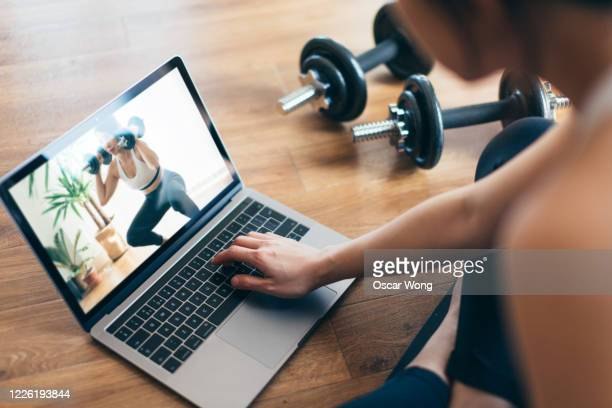young woman practising weight training workout with a video lesson on laptop. - relaxation exercise stock pictures, royalty-free photos & images