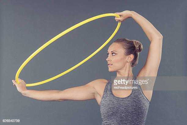 Young woman practising with hula hoop, grey background