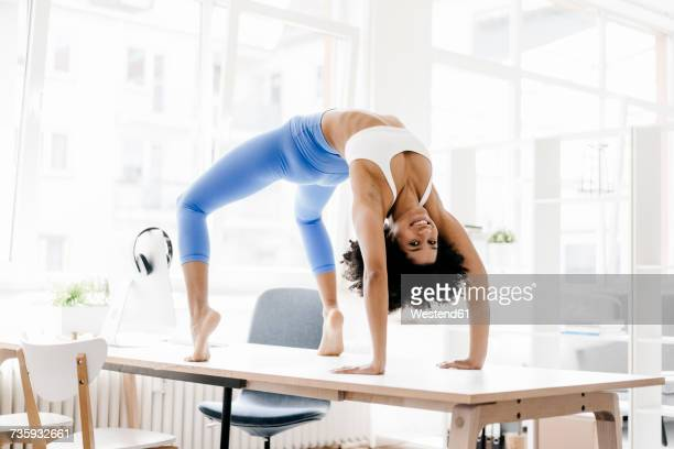 Young woman practising yoga on her desk