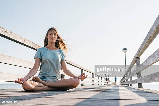 Young woman practising yoga on jetty