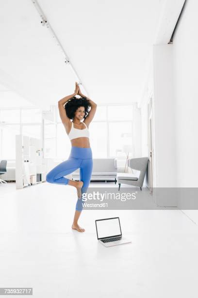 Young woman practising yoga with laptop by her side