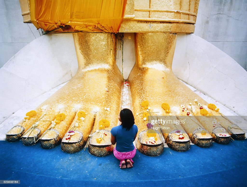Young Woman Praying at Feet of Giant Buddha Statue : Stock Photo