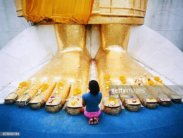 young woman praying at feet of giant buddha statue - big foot stock photos and pictures