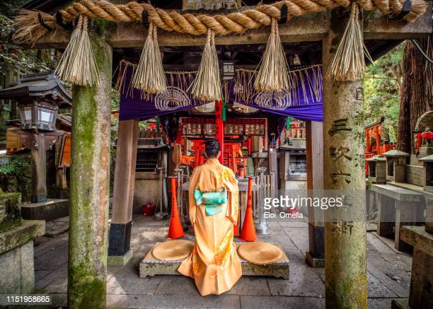 young woman praying at fushimi inari taisha temple, kyoto, japan - shinto shrine stock pictures, royalty-free photos & images