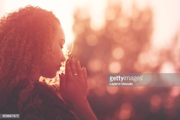 young woman praying - praying stock pictures, royalty-free photos & images