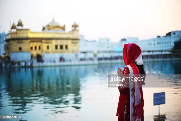 young woman praying to god in golden temple, india - amritsar stock pictures, royalty-free photos & images