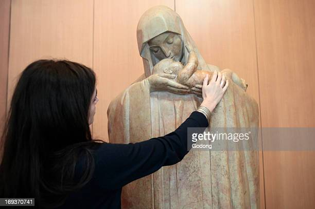 Young woman praying to the Virgin Mary