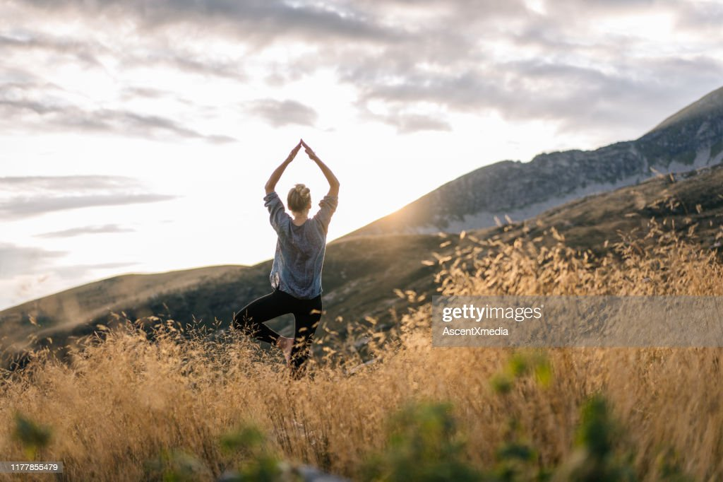Young woman preforms yoga in mountains in morning light : Stock Photo