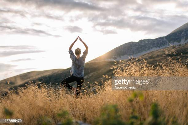 young woman preforms yoga in mountains in morning light - spirituality stock pictures, royalty-free photos & images