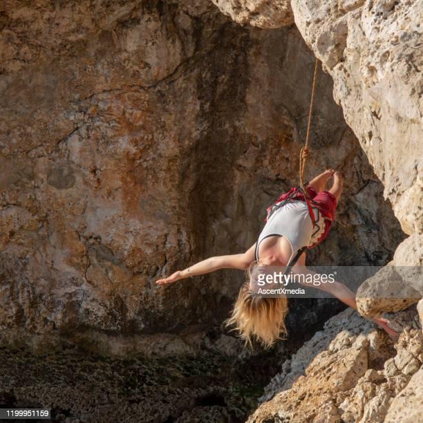 la jeune femme préforme le yoga se déplace tandis que suspendu sur l'extrémité d'une corde au-dessus d'une caverne - blonde forte poitrine photos et images de collection