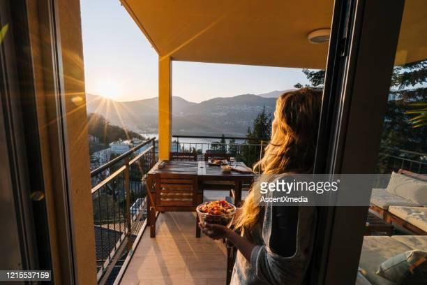 junge frau bereitet gesunde mahlzeit auf der terrasse zu - aussicht genießen stock-fotos und bilder