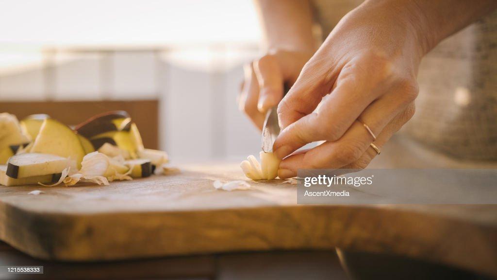 De jonge vrouw bereidt gezonde maaltijd op terras voor : Stockfoto