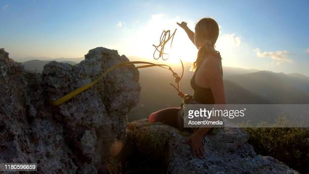 young woman prepares to descend, throws rope from summit - risk stock pictures, royalty-free photos & images