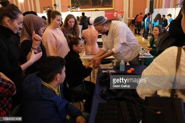 A young woman prepares to don gloves with a mild electric current that are meant to simulate the effect of Parkinson's disease at a jobs fair for...