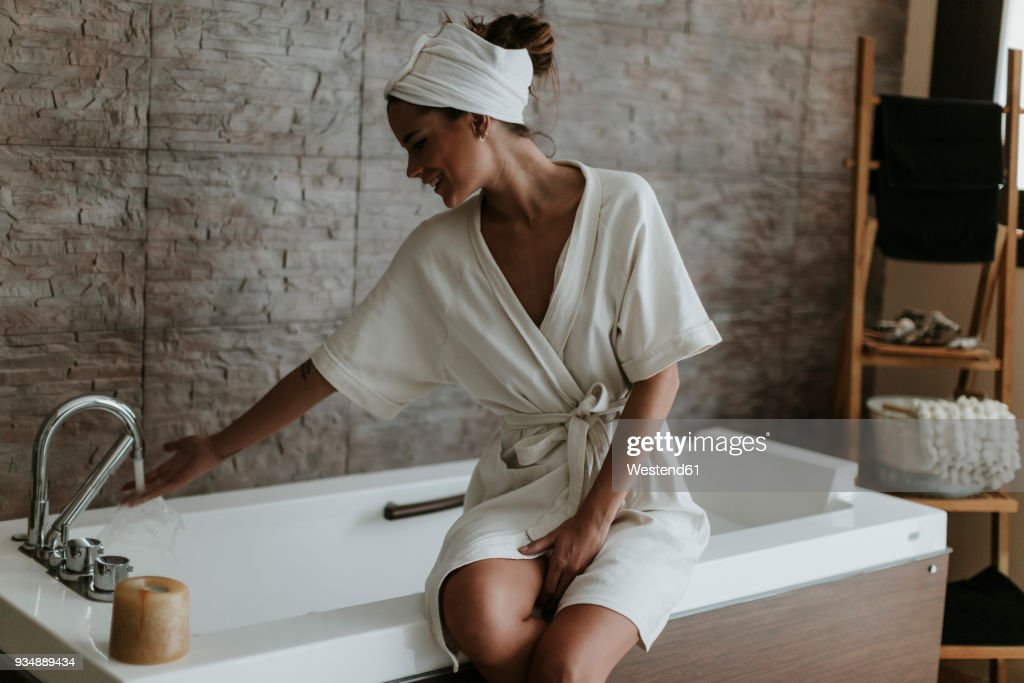 Young woman preparing a bath in a spa : Stock Photo