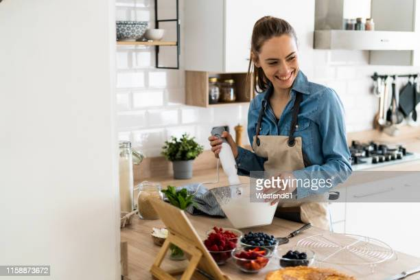 young woman preparing a cream cake, using tablet - fruit cake stock pictures, royalty-free photos & images