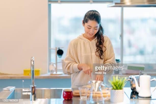 キッチンで朝食を準備する若い女性 - 料理 ストックフォトと画像
