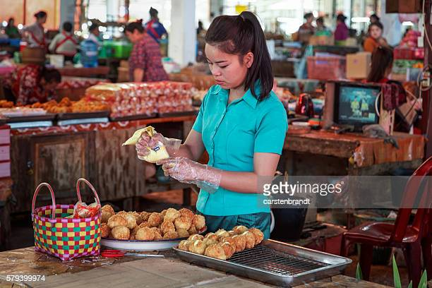 Young woman preparing cakes in the  market in Phonsavan