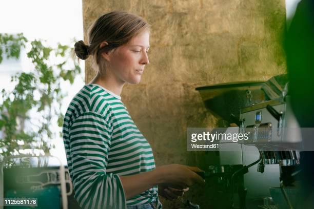 young woman preparing coffee in a cafe - junge frau allein stock-fotos und bilder