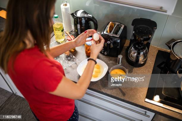 young woman preparing dinner - electric stove burner stock pictures, royalty-free photos & images