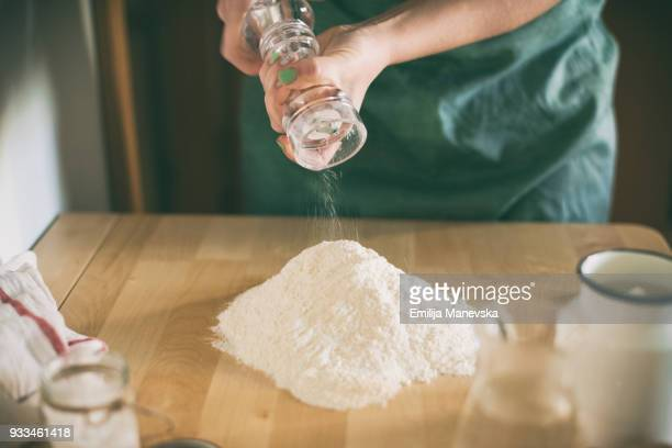 Young woman preparing dough in kitchen