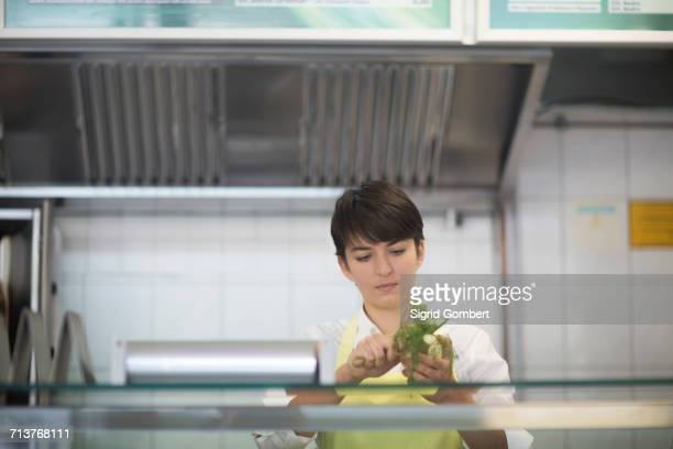 young woman preparing food in fast food shop - sigrid gombert stock pictures, royalty-free photos & images