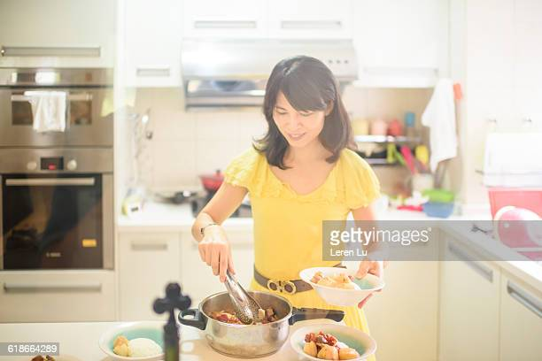 young woman preparing food in kitchen - long bright yellow dress stock pictures, royalty-free photos & images