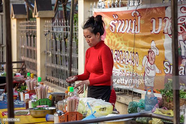 Young woman preparing food in the night market in Luang Prabang