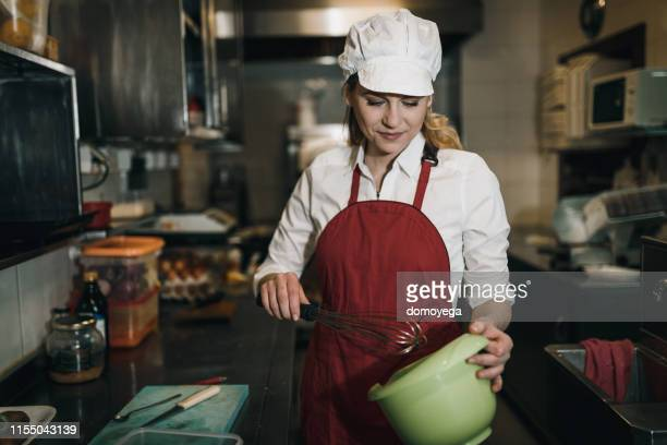 junge frau bereitet essen in der küche des restaurants zu - female whipping stock-fotos und bilder