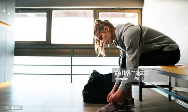 ロッカールームでトレーニングの準備をしている若い女性 - ロッカールーム ストックフォトと画像