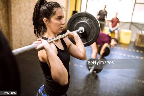 young woman preparing for weightlifting - girl power stock photos and pictures