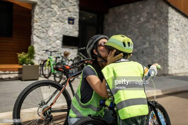 jonge vrouw die haar zoon voor fiets het berijden voorbereidt - vest stockfoto's en -beelden