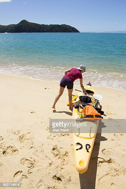 Young woman preparing kayak on beach, Abel Tasman National Park
