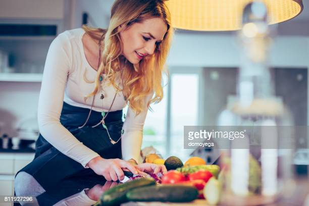 Jeune femme prépare le repas dans la recette de cuisine et de la lecture de la tablette numérique