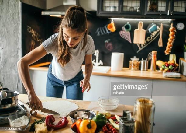 ung kvinna förbereda pizza - endast en ung kvinna bildbanksfoton och bilder