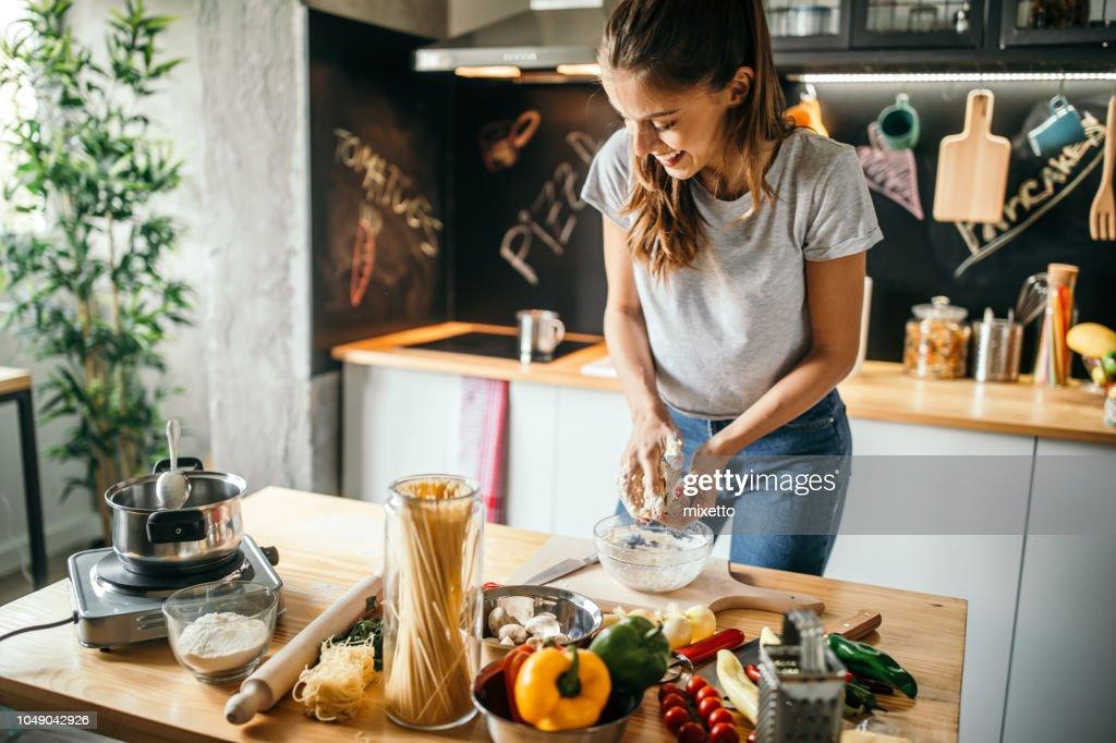 Jovem mulher preparando pizza : Foto de stock