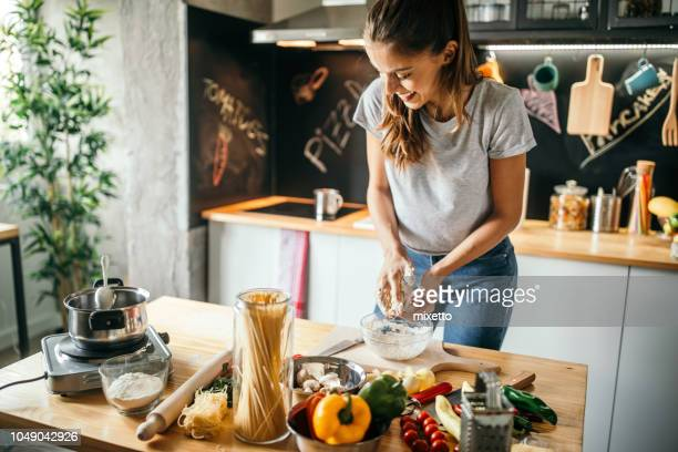young woman preparing pizza - kitchen stock pictures, royalty-free photos & images