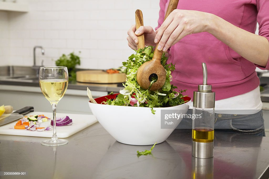 Young woman preparing salad in kitchen, mid section : Stock Photo