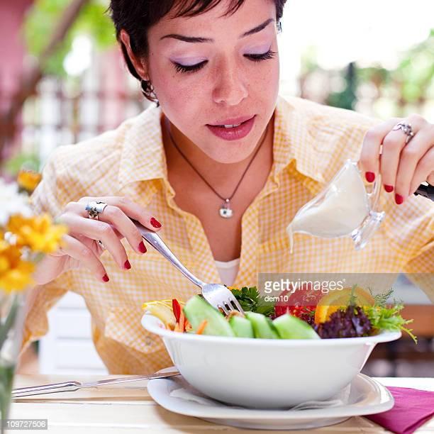 Jeune femme préparant la salade
