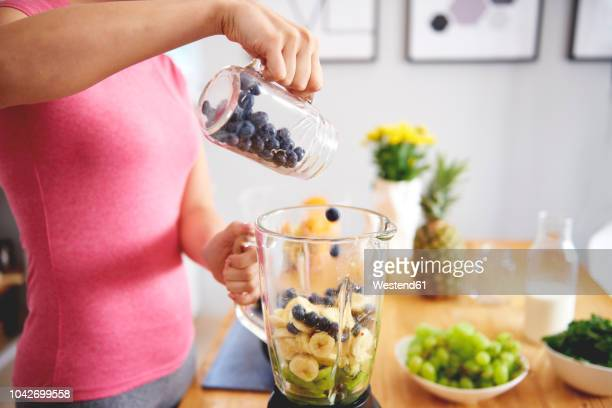 Young woman preparing smoothie in the kitchen, partial view