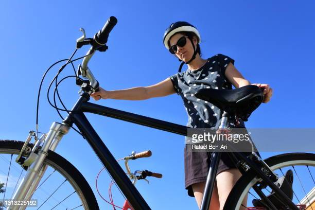 young woman preparing to go on a bike ride - rafael ben ari stock-fotos und bilder