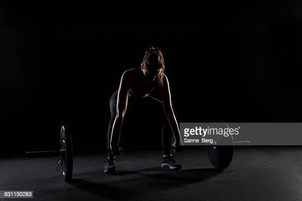 young woman preparing to lift a barbell in gym - sportgerät stock-fotos und bilder