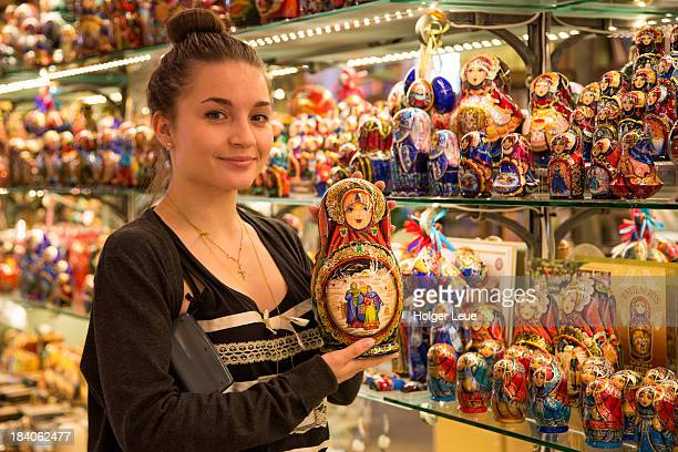 Young woman presents Matryoshka doll for sale